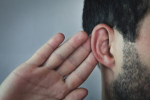 Man putting hand up to ear to hear